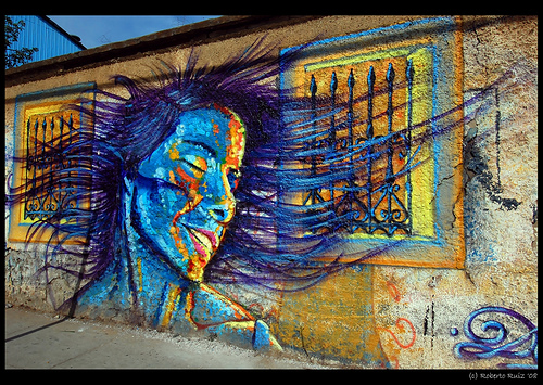 Painted woman, head shaking, hair blowing, in beautiful blue and yellow colors.